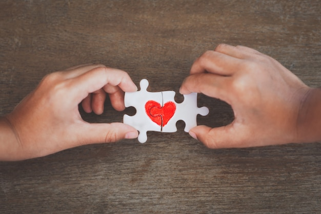 Twee jonge geitjeshanden die het stuk van de paarpuzzel met getrokken rood hart verbinden