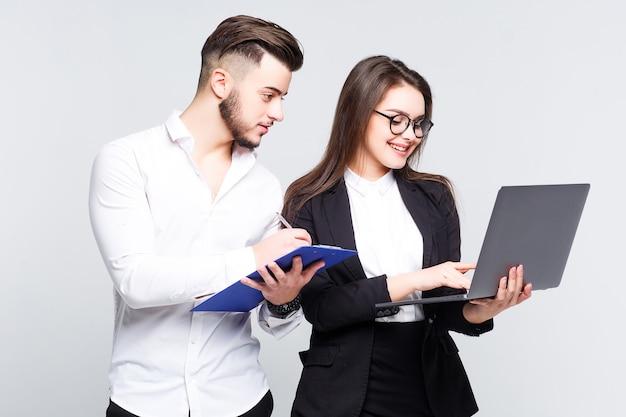 Twee jonge gelukkig lachende succesvolle zakenmensen werken met laptop op witte muur