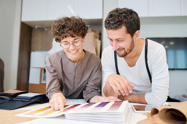 Twee jonge gelukkig modeontwerpers kijken naar een van de kleurstalen in de catalogus terwijl ze erover praten