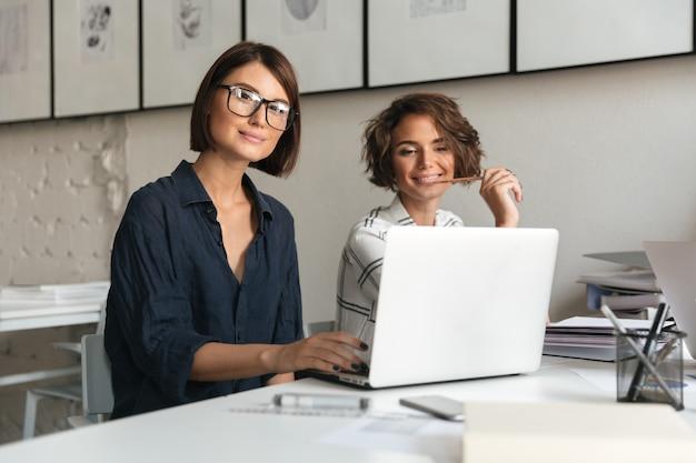 Twee jonge gelukkig vrouwen werken bij de tafel