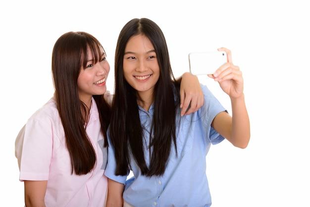 Twee jonge gelukkige aziatische tienermeisjes die en selfie glimlachen nemen