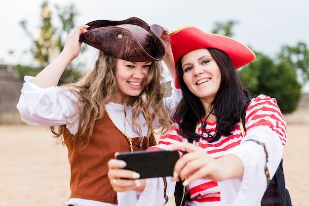 Twee jonge gelukkige glimlachende kaukasische vrouwen in piraatkostuums die selfie op smartphone nemen.