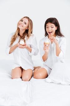 Twee jonge gelukkige meisjes in witte overhemden die zoete cupcakes eten