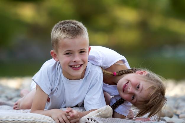 Twee jonge gelukkige schattige blonde lachende kinderen, jongen en meisje, broer en zus leggen omarmd op kiezelstrand op wazig heldere zonnige zomerdag scène. vriendschap en perfect vakantieconcept.