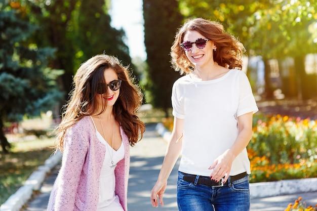 Twee jonge gelukkige vrouwen die in het de zomerpark lopen