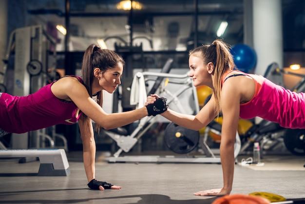 Twee jonge gemotiveerde agressieve aantrekkelijke gerichte sportieve actieve vrouw doen push-ups en houden handen bij elkaar terwijl ze elkaar in de moderne sportschool kijken.
