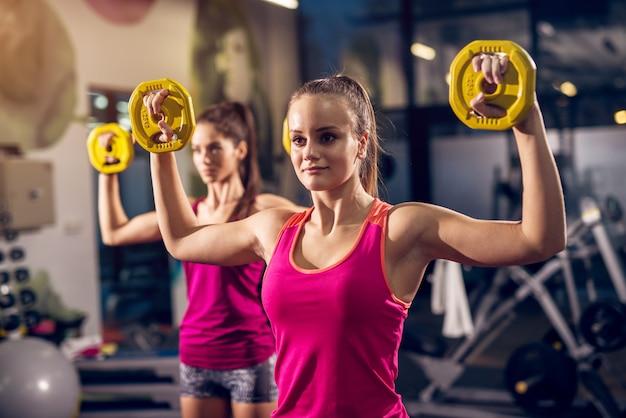 Twee jonge gemotiveerde atletische aantrekkelijke gerichte sportieve actieve vrouw doen oefeningen met gewichten terwijl open armen in de moderne sportschool hebben opgeheven.
