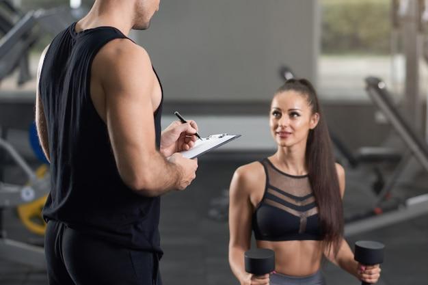 Twee jonge geschikte mensen die in gymnastiek werken.