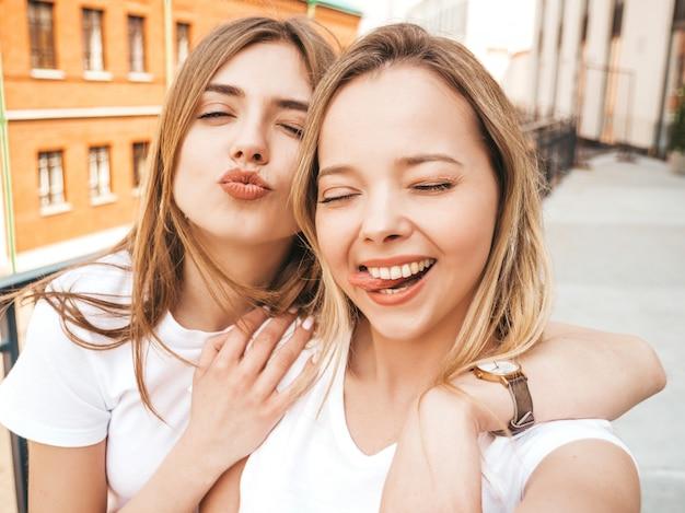 Twee jonge glimlachende hipster blonde vrouwen in de zomerkleren. meisjes nemen selfie zelfportretfoto's op smartphone. .