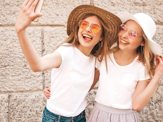 Twee jonge glimlachende hipster blonde vrouwen in kleren van de de zomer de witte t-shirt. meisjes nemen selfie zelfportretfoto's op smartphone.