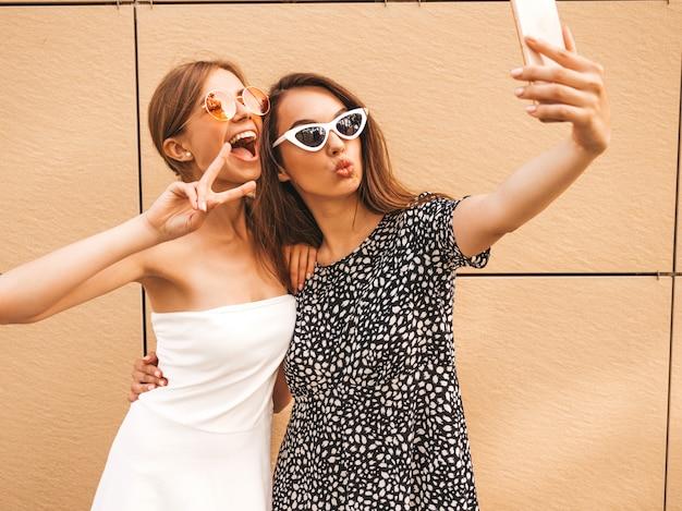 Twee jonge glimlachende hipster vrouwen in de zomerkleren.