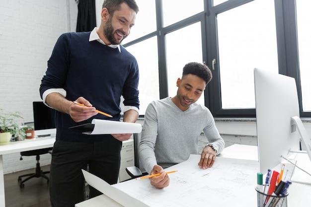 Twee jonge glimlachende mannelijke arbeiders die met documenten samenwerken