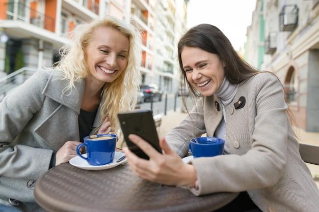 Twee jonge glimlachende vrouwen die pret in openluchtkoffie hebben