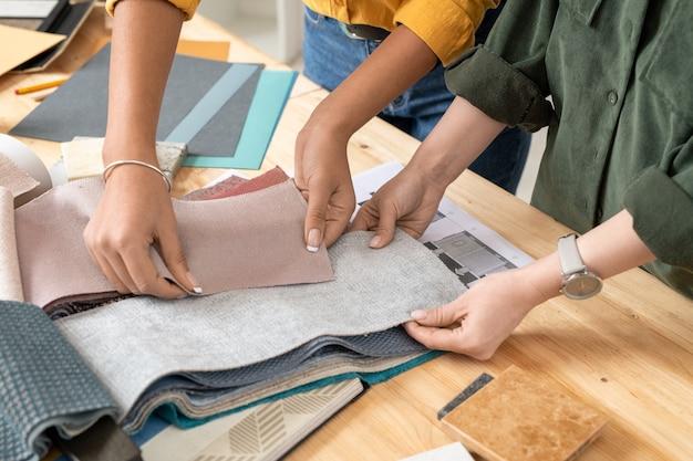 Twee jonge hedendaagse vrouwelijke interieurontwerpers kijken door stalen van meubeltextiel