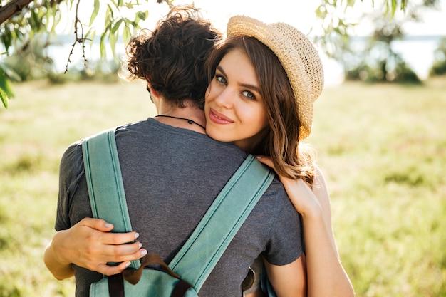 Twee jonge hipster liefhebbers knuffelen in het bos