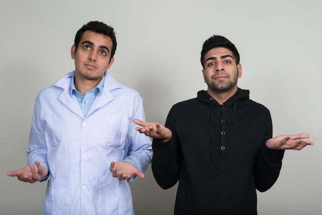 Twee jonge indiase mannen als arts en patiënt samen tegen witte muur