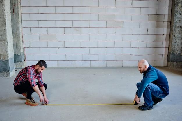Twee jonge ingenieurs die op kraakpanden zitten en de opening van de deur meten terwijl ze in een onafgewerkt gebouw werken
