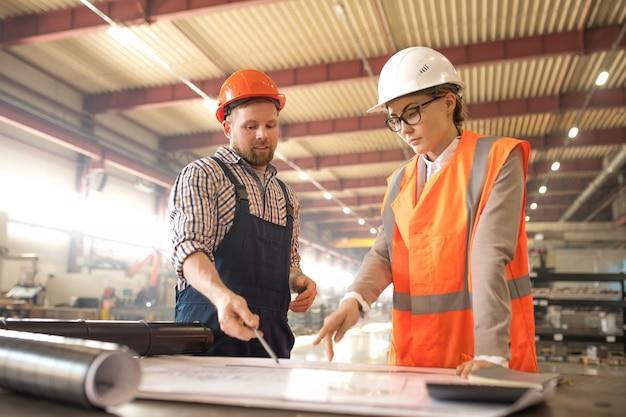 Twee jonge ingenieurs in helmen en uniform wijzend op blauwdruk van industriële details op werkvergadering