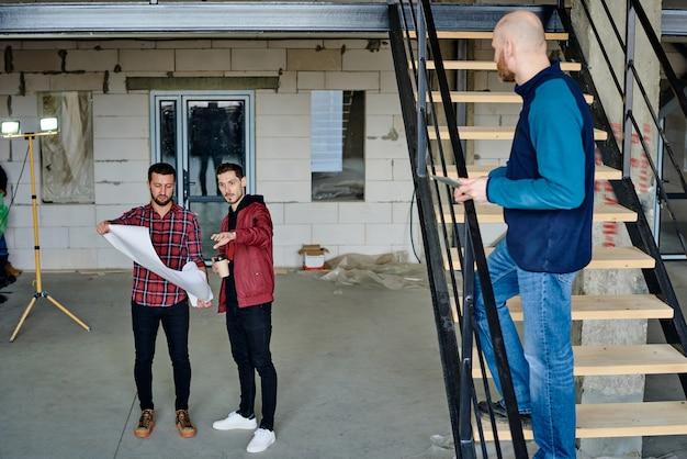 Twee jonge ingenieurs met blauwdruk bespreken de details van de schets, terwijl een van hen uitlegt wat er aan de constructie kan worden veranderd