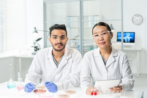 Twee jonge interculturele clinici in witte jassen kijken door online gegevens terwijl ze monsters van rauw plantaardig vlees in het laboratorium bestuderen