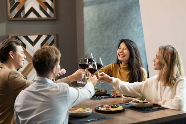 Twee jonge interculturele koppels in slimme vrijetijdskleding rammelend met glazen rode wijn over tafel geserveerd tijdens het diner in luxe restaurant