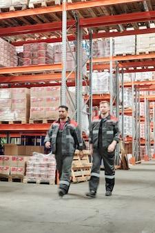 Twee jonge interculturele mannelijke arbeiders in uniform bewegen langs grote fabriek of magazijn met enorme planken met ingepakte goederen