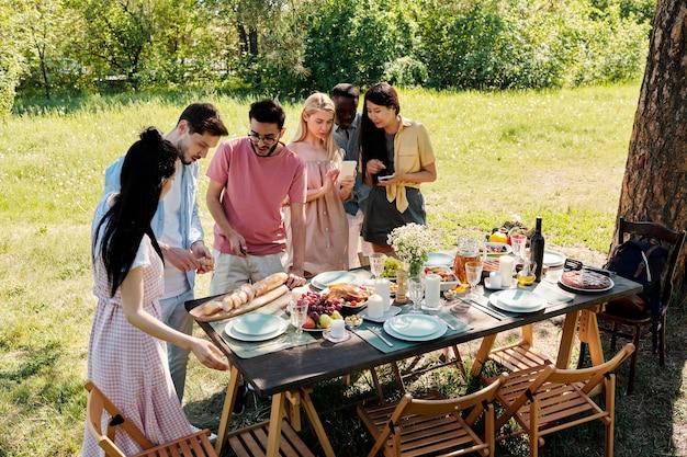 Twee jonge interculturele mannen praten terwijl een van hen vers stokbrood op tafel snijdt onder hun vriendinnen voordat ze buiten eten
