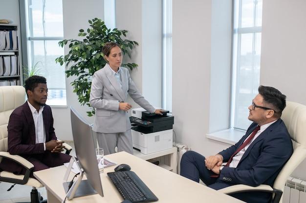 Twee jonge interculturele ondergeschikten in overleg met hun zelfverzekerde directeur in functie