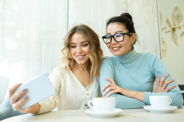 Twee jonge interculturele vrouwtjes smartphone camera kijken met een glimlach terwijl het maken van serlfie door kopje koffie in café