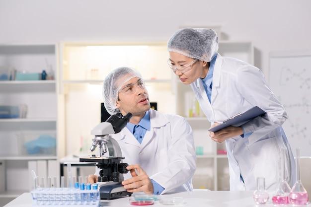 Twee jonge interculturele wetenschappers in whitecoats die in het laboratorium overleggen terwijl ze aan een nieuw vaccin werken en virussen bestuderen