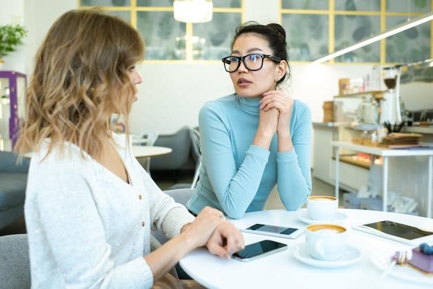 Twee jonge interculturele zakenvrouwen in vrijetijdskleding werken punten of plannen bespreken terwijl het hebben van koffie bij tafel in café