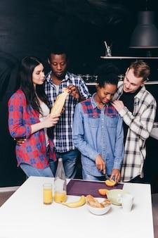 Twee jonge interraciale gelukkige koppels koken samen