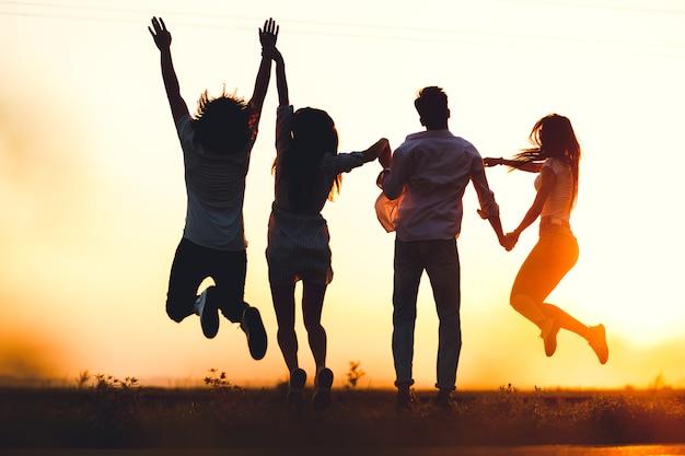 Twee jonge jongens en twee meisjes houden hun hand vast en springen op een zomerdag in het veld