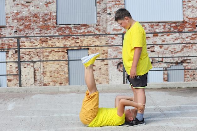 Twee jonge jongens in gele t-shirts trainen. trainen van buikspieren. hoge kwaliteit foto