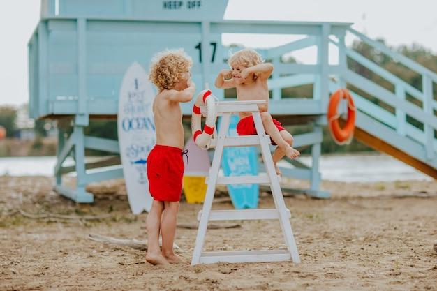 Twee jonge jongens in rode zwembroek en een zittend op de strandwachtstoel op het strand