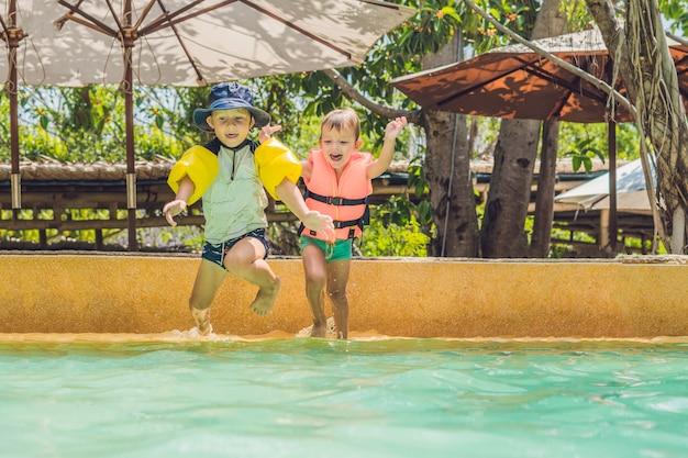 Twee jonge jongensvrienden die in het zwembad springen
