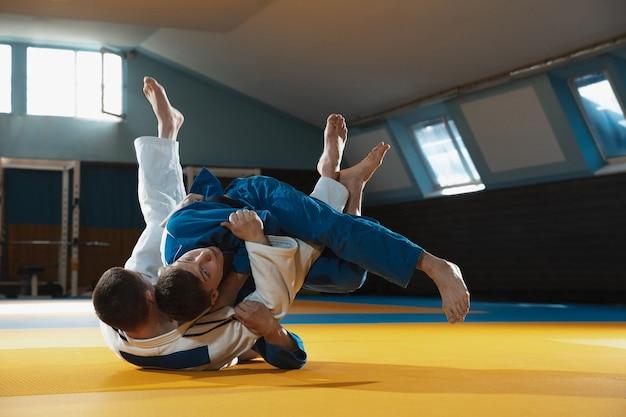 Twee jonge judo-vechters in kimono die vechtsporten opleiden in de gymnastiek met expressie in actie en beweging