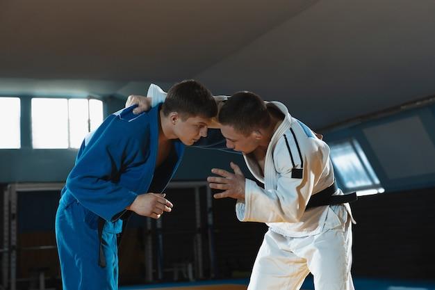 Twee jonge judovechters in kimono die vechtsporten trainen in de sportschool