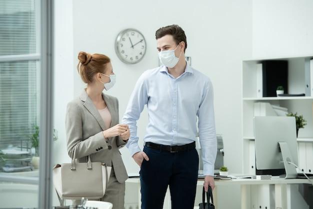 Twee jonge kantoormanagers of ontwerpers met beschermende maskers en formele kleding bespreken na hun werk plannen terwijl ze samen tijd doorbrengen