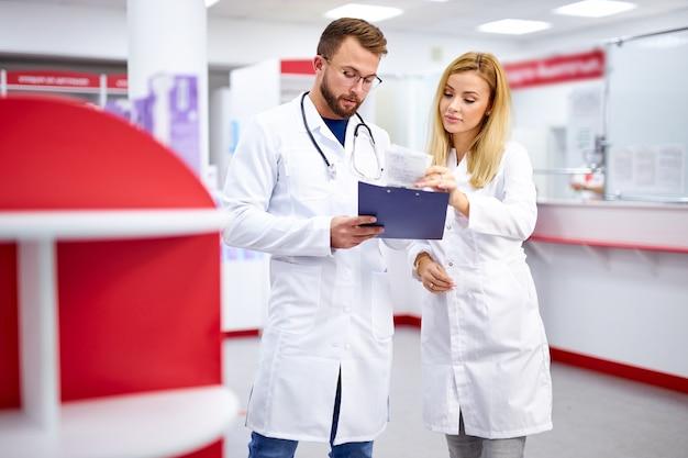 Twee jonge kaukasische apothekers bespreken medicatie