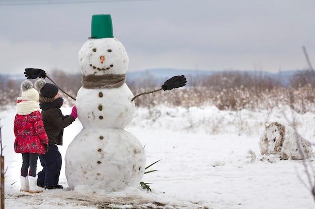 Twee jonge kinderen, jongen en meisje, eindigen met het doen van lachende sneeuwpop in emmerhoed, sjaal en handschoenen op leeg winterveldlandschap en blauwe luchtkopieerruimteachtergrond. vrolijk kerstfeest gelukkig nieuwjaar.
