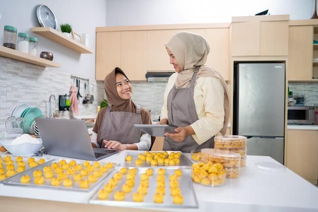 Twee jonge kleine moslimbedrijfseigenaar die zelfgemaakte nastartaart van huis verkoopt. moslimvrouw samen ananastaart bakken