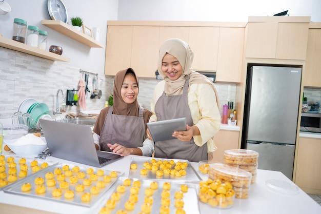Twee jonge kleine moslimondernemers die zelfgemaakte nastarcake vanuit huis verkopen. moslimvrouw samen ananastaart bakken voor eid mubarak