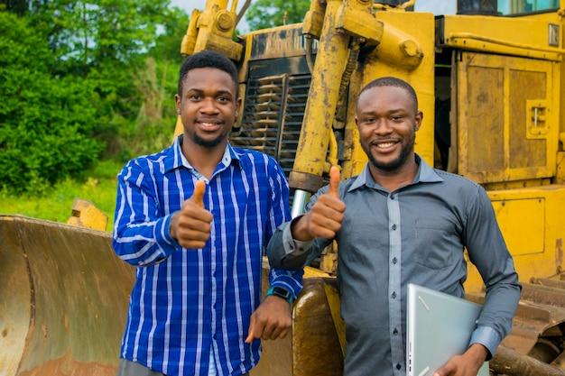 Twee jonge knappe afrikaanse aannemers voelen zich overweldigd terwijl ze naast een tractor staan en duimen omhoog