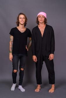 Twee jonge knappe mannen samen tegen grijze muur