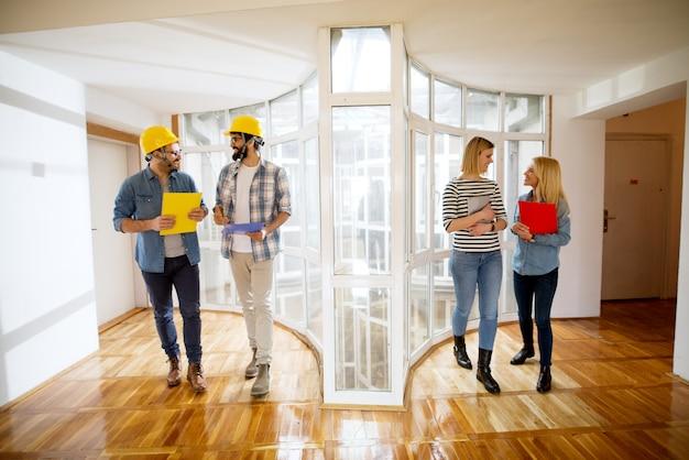 Twee jonge lachende mannelijke ingenieurs en twee blonde designermeisjes die vrolijk door de lichte gang lopen.