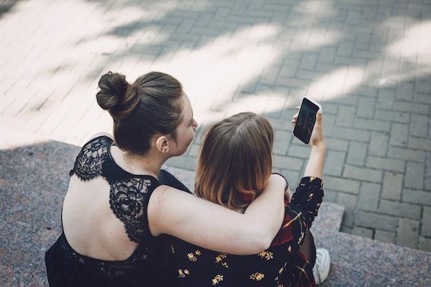 Twee jonge lesbiennes meisjes knuffelen en nemen selfie op smartphone buitenshuis.