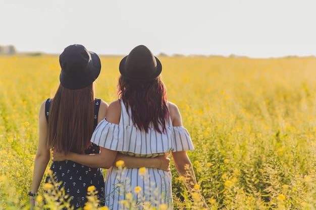 Twee jonge lesbische vrouwen op het veld die jurken dragen.