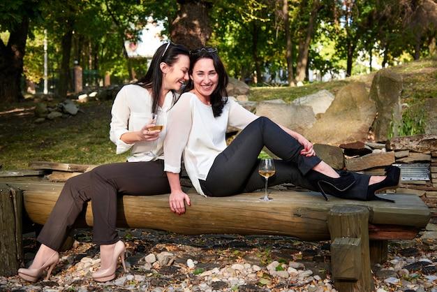 Twee jonge leuke meisjes die op logboeken zitten die wijn en het lachen drinken