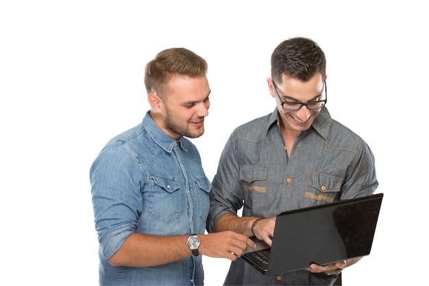 Twee jonge man op zoek op een laptop pc, glimlachend